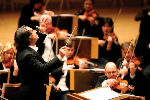 Muti conducting with violinists playing behind him