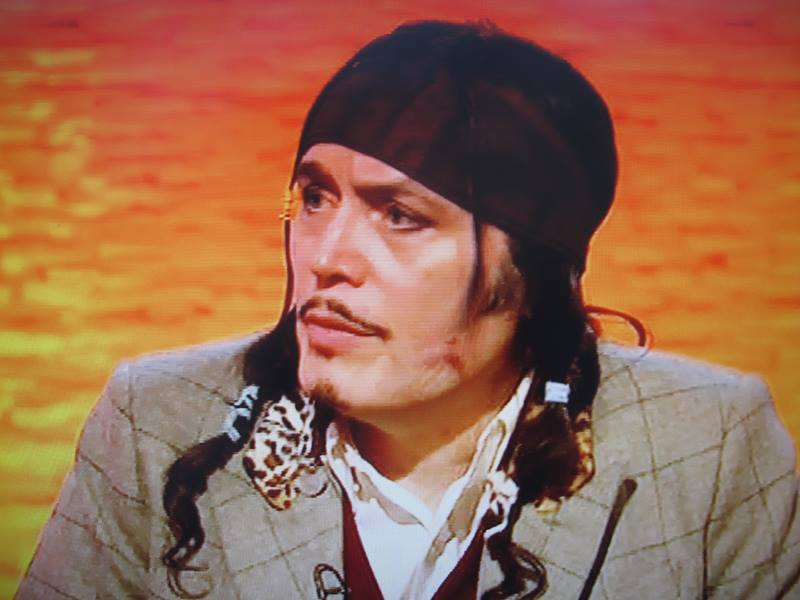 Adam Ant looking to his side in front of an orange background