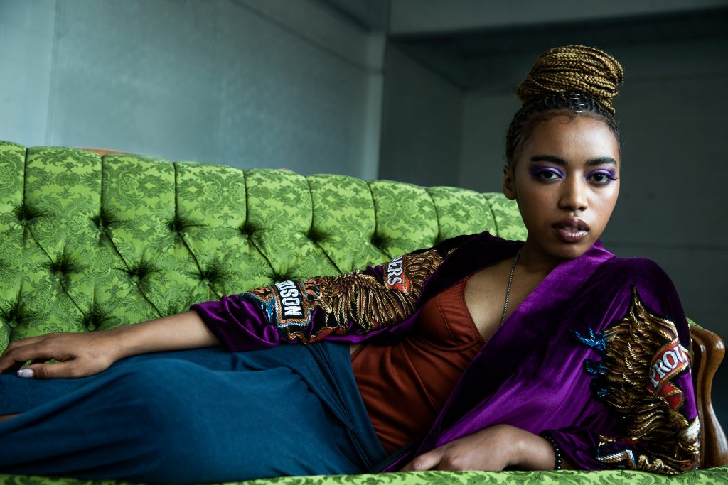 Jean Deaux laying on a green couch